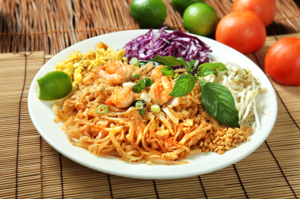 plate of noodles with shrimp, cabbage, bean sprouts and lime wedge