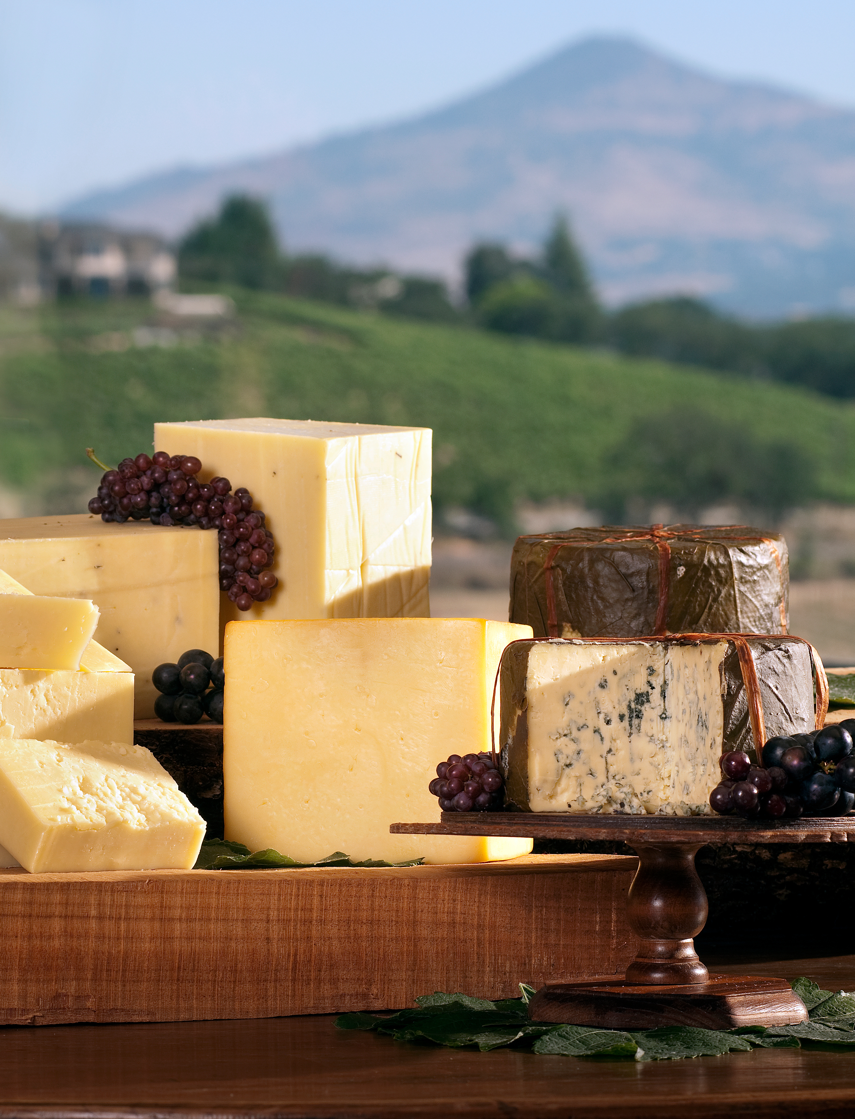 close up of cheese board with cheese and grapes with mountain in background