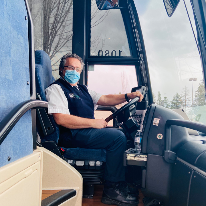 driver of motorcoach bus with surgical mask on