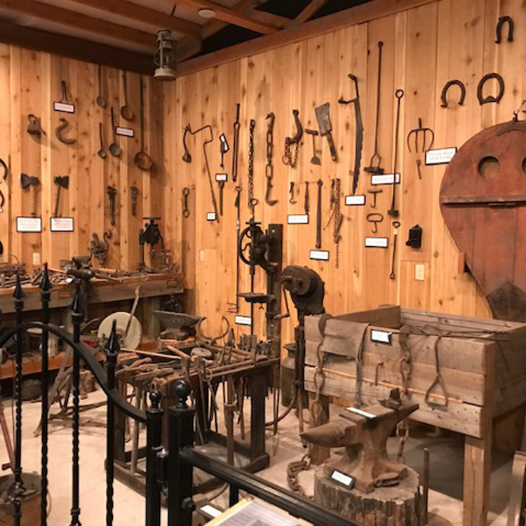 museum display of a livery with horseshoes and tools on the wall