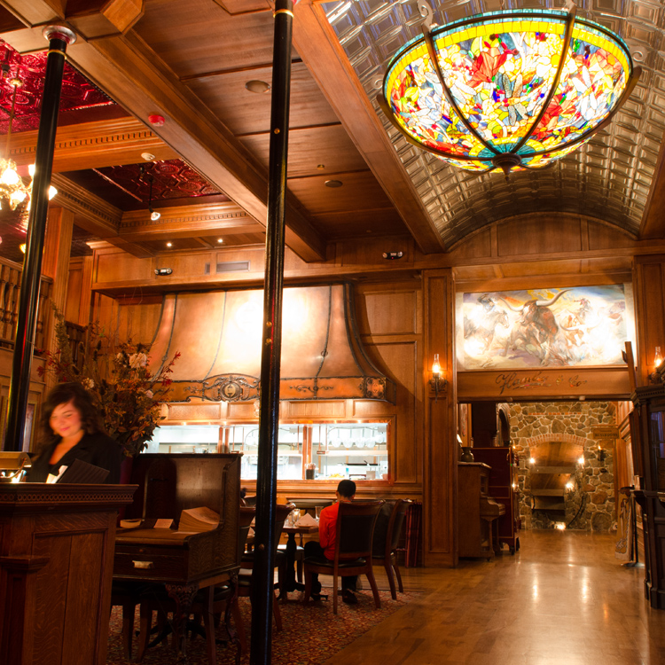 seating area at restaurant with view into kitchen and large stained glass light fixture above