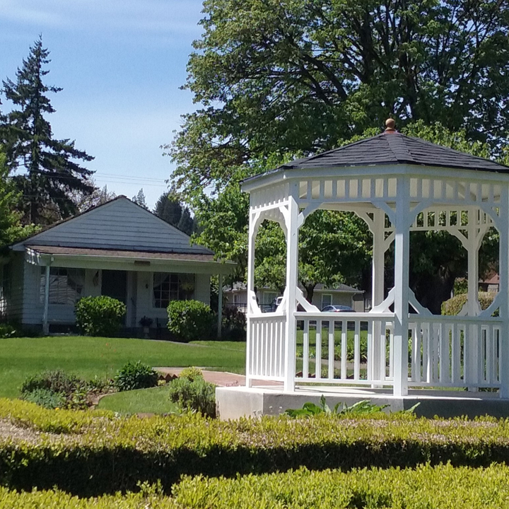 gazebo surrounded by grass with cottage in the background