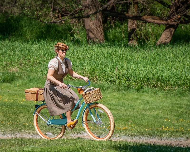 Woman in tweed dress riding bike on sunny day