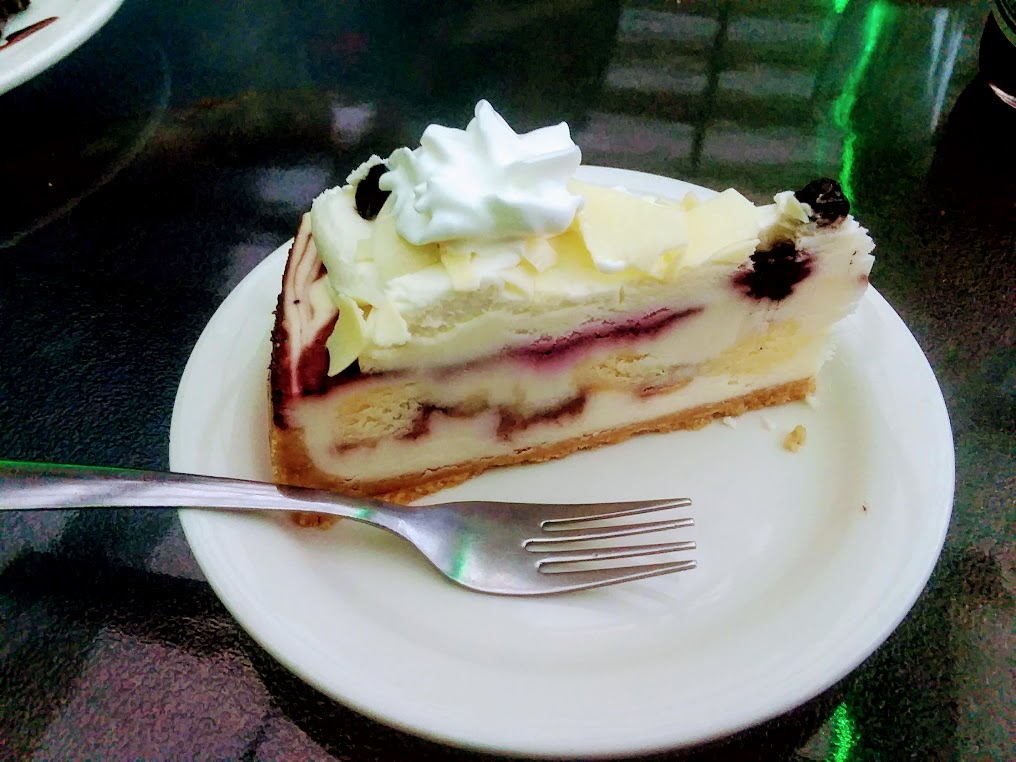 White chocolate and blueberry cheesecake with whipped cream on white plate