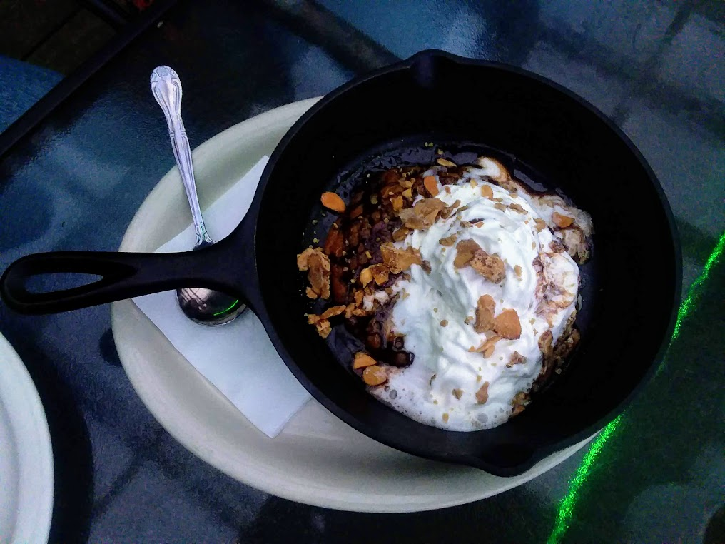 individual cast iron skillet with chocolate chip cooke topped with vanilla ice cream and whipped cream