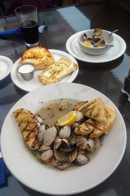 butter clams in white wine and garlic, toast and lemon garnish on white dishes