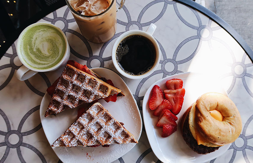 A table with a waffle sandwich, a breakfast sandwich and coffee drinks