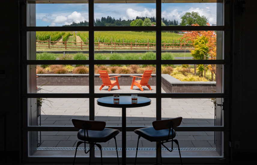 An empty bistro table overlooking a patio and vineyard.