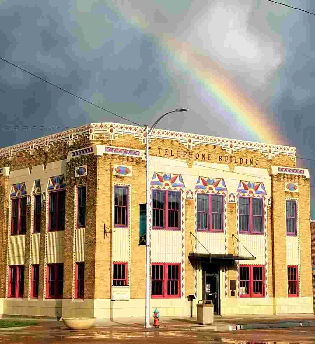 Old brick building with rainbow behind it
